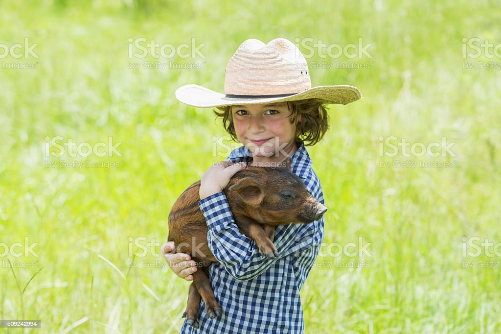 Little boy with cowboy hat holding baby pig stock photo