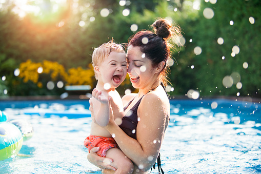 Three years old Little boy with Down syndrome having fun in the swimming pool with his family.  Her mother holds him in her arms. Color and horizontal Photo was taken in Quebec Canada.