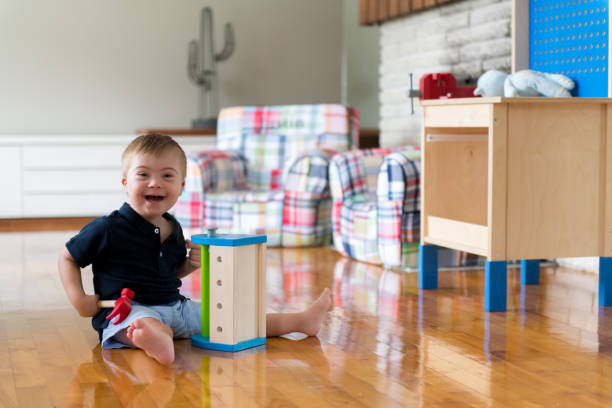 little boy with down syndrome plays with wooden toy bench - manonallard stock photos and pictures