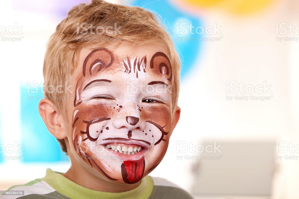 Little boy with face painted as lion on birthday party royalty-free stock photo