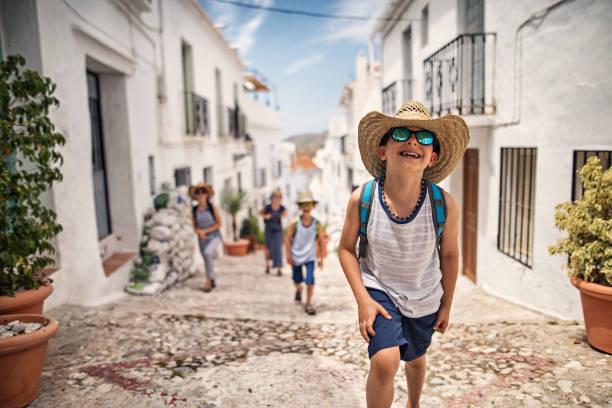 petit garçon avec le village andalou blanc visite familiale - andalousie photos et images de collection