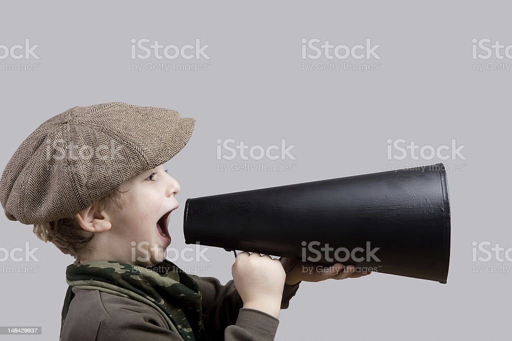 Little boy with flat cap shouting on old fashioned megaphone stock photo