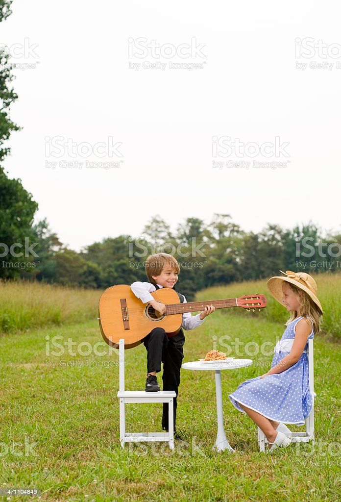 Little boy with foot on chair plays guitar for girl royalty-free stock photo