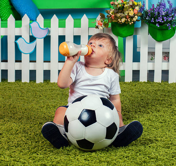 Little boy with football drinking milk from bottle stock photo