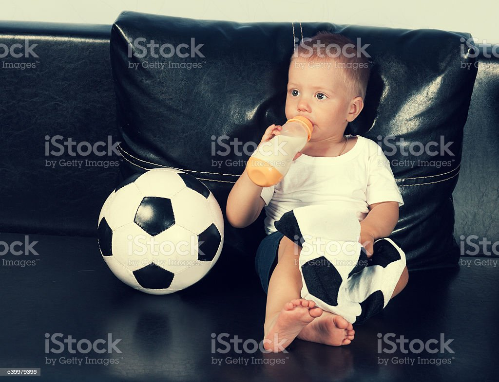 Little boy with fútbol beber leche de botella - foto de stock