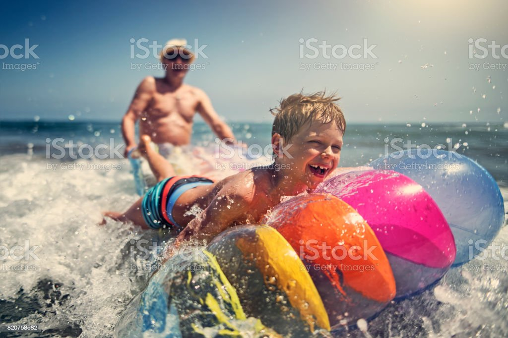 Little boy with grandfather playing in sea waves stock photo