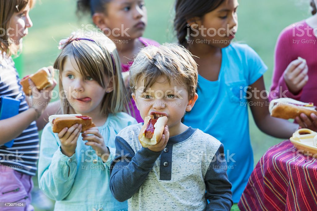 Little boy with group of children eating hotdogs stock photo