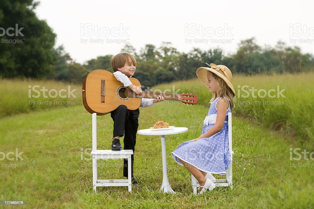 Little boy with guitar serenades girl sitting at table royalty-free stock photo