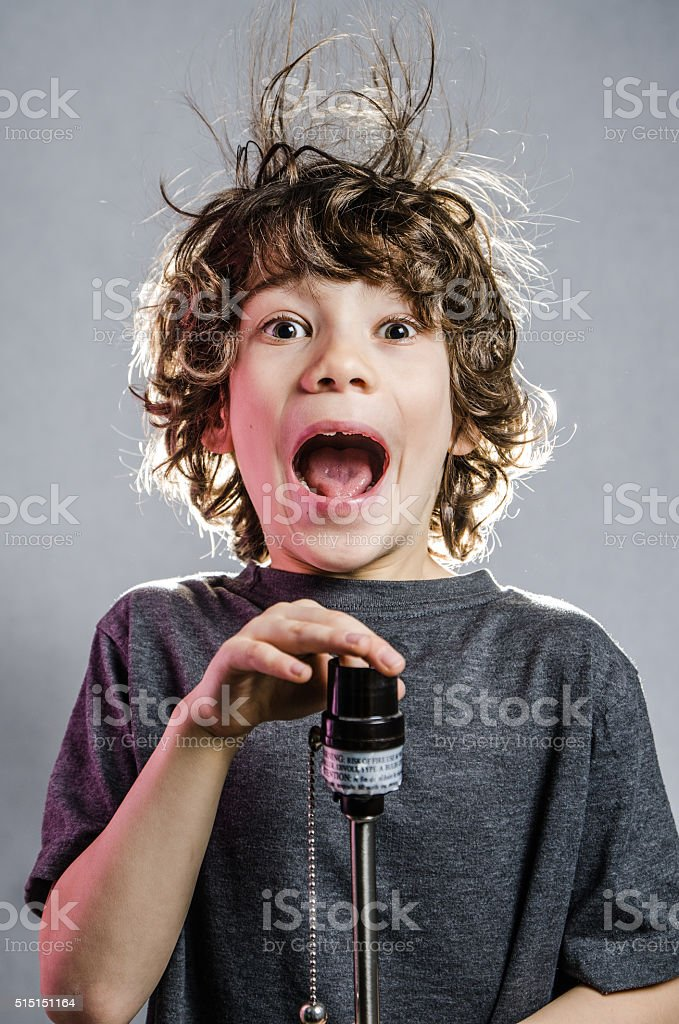 Little boy with hair electrified with finger in light socket stock photo