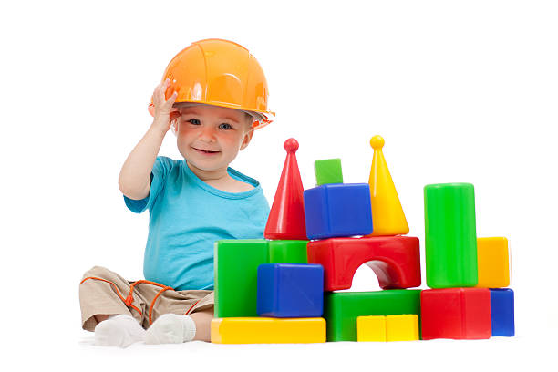 little boy with hard hat playing building blocks stock photo