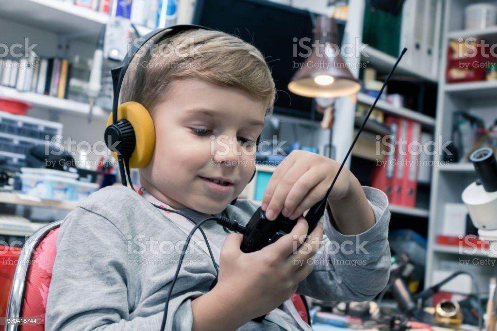 Little boy with headphones using walkie talkie. stock photo