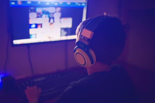 kleiner junge mit kopfhörer mit computer - online spiele spielen stock-fotos und bilder