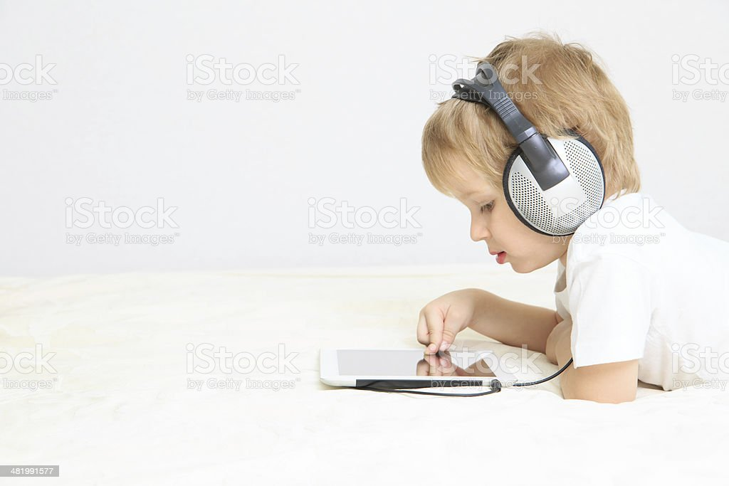 little boy with headset using touch pad stock photo