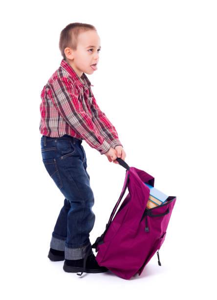 Little boy with heavy schoolbag stock photo
