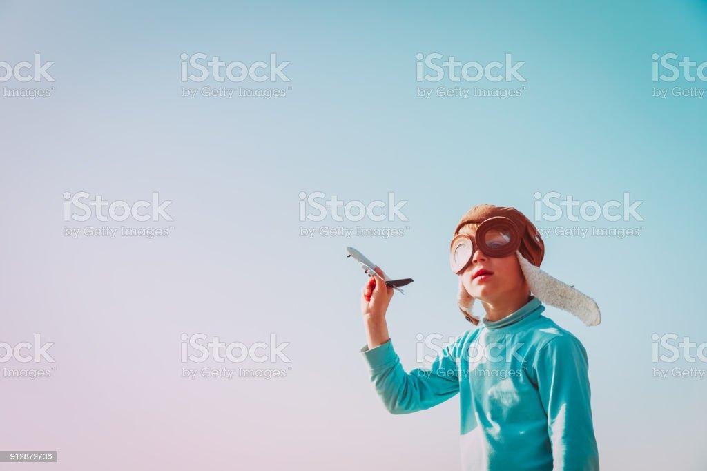 ヘルメットとグラスを持った少年が空におもちゃの飛行機で遊ぶ ストックフォト