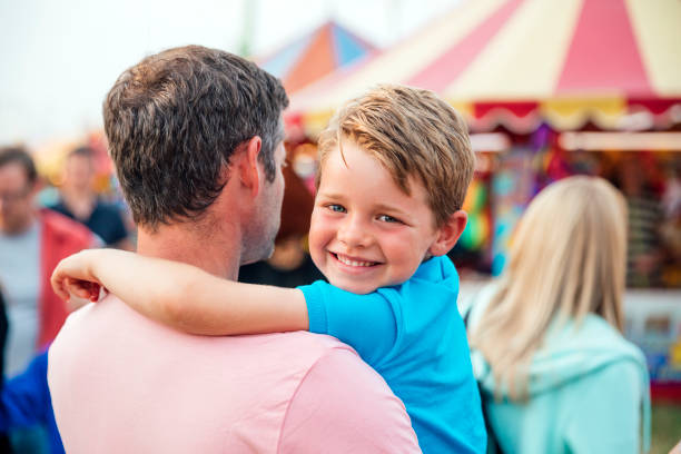 Little Boy with his Dad at an Amusement Park stock photo