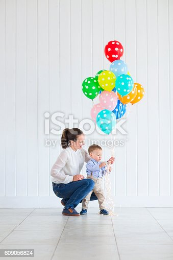 istock Little boy with his mom holding bunch of colored balloons 609056824
