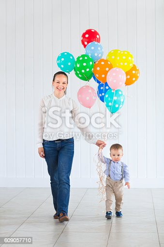 609058672 istock photo Little boy with his mom holding bunch of colored balloons 609057710