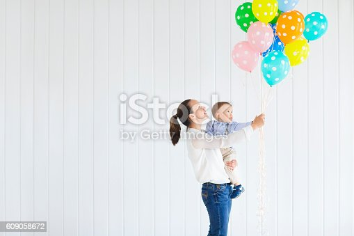 istock Little boy with his mom holding bunch of colored balloons 609058672