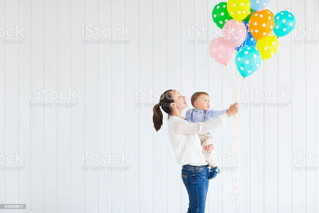 Little boy with his mom holding bunch of colored balloons stock photo