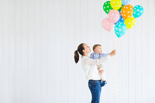 little boy with his mom holding bunch of colored balloons - baby party stock-fotos und bilder