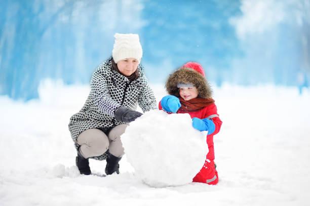 kleiner junge mit seiner mutter/babysitter/großmutter gebäude schneemann im verschneiten park - schneemann bauen stock-fotos und bilder