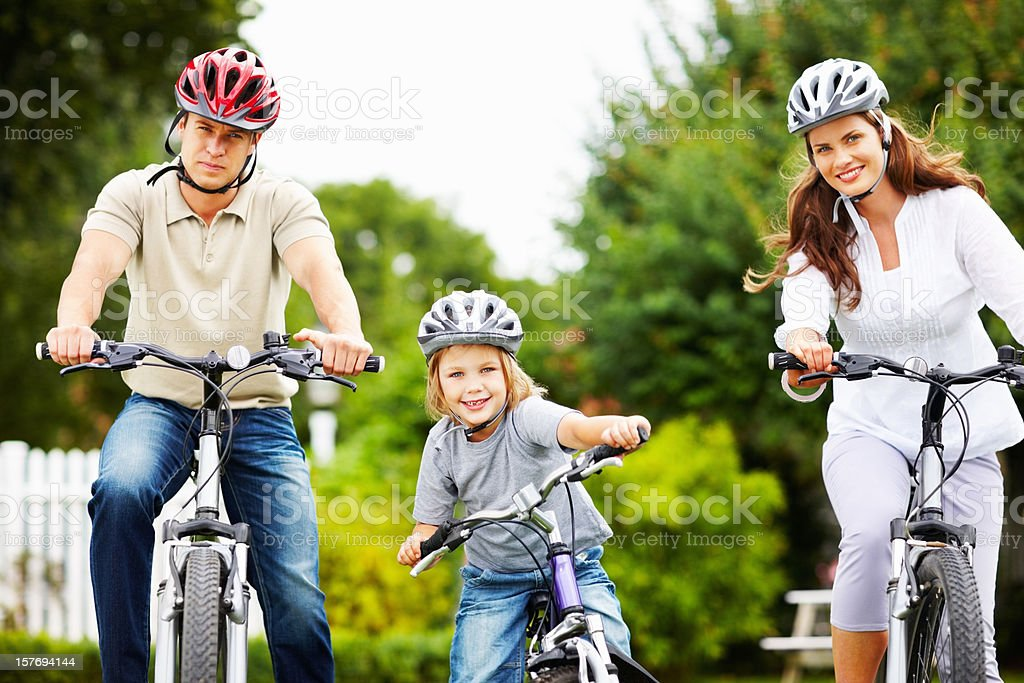 Little boy with his parents riding bicycle royalty-free stock photo