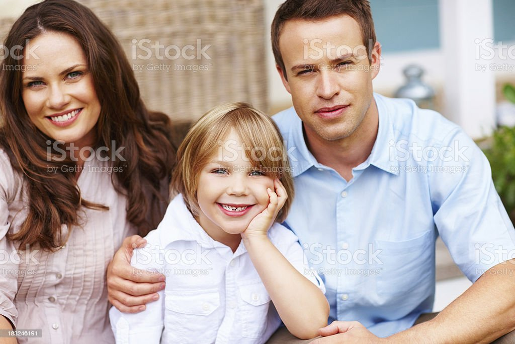 little boy with his parents sitting in front of house royalty-free stock photo