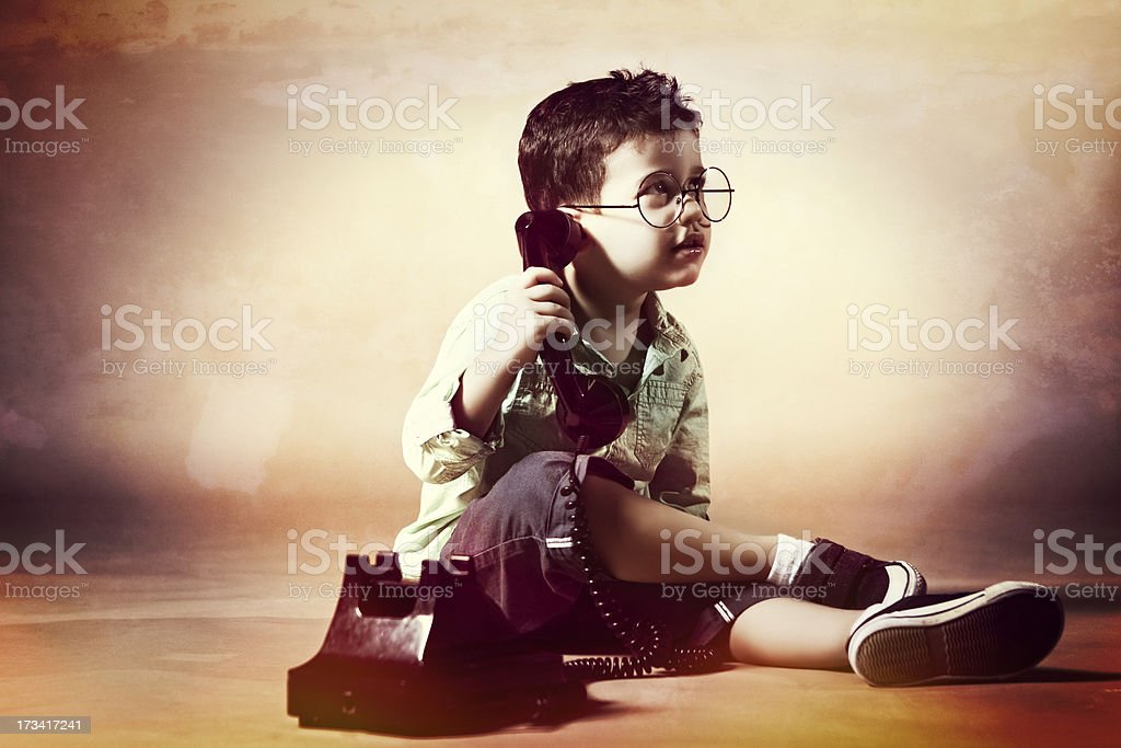 Little boy with horn rimmed glasses on the phone royalty-free stock photo
