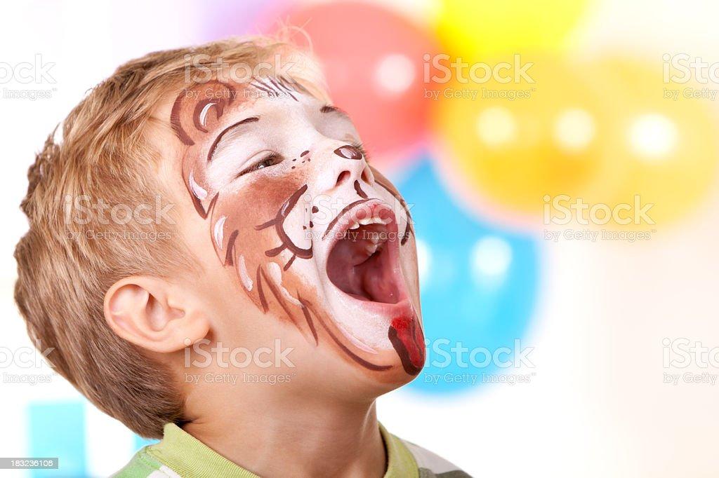 Menino com rosto de leão na festa de aniversário - foto de acervo