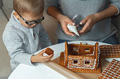istock Little boy with mom decorate christmas gingerbread house togethe 1284809389