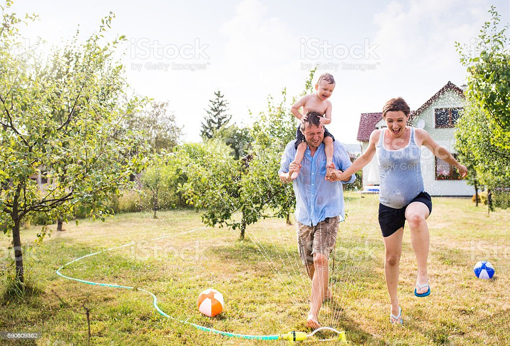Little boy with mother and father at the sprinkler - Photo