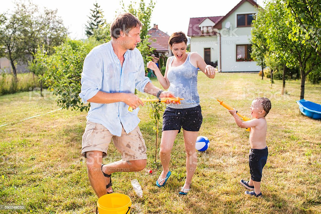 Little boy with mother and father splashing each other stock photo
