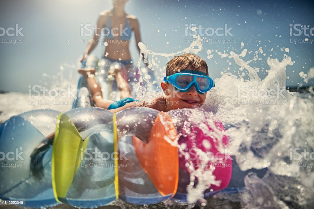 Little boy with mother playing having fun in sea stock photo