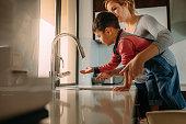 Little boy with mother washing hands in kitchen sink