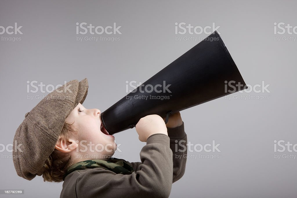 Little boy with newsboy cap shouting on old fashioned megaphone stock photo