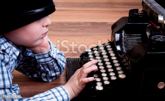little boy with old type writer writing letter