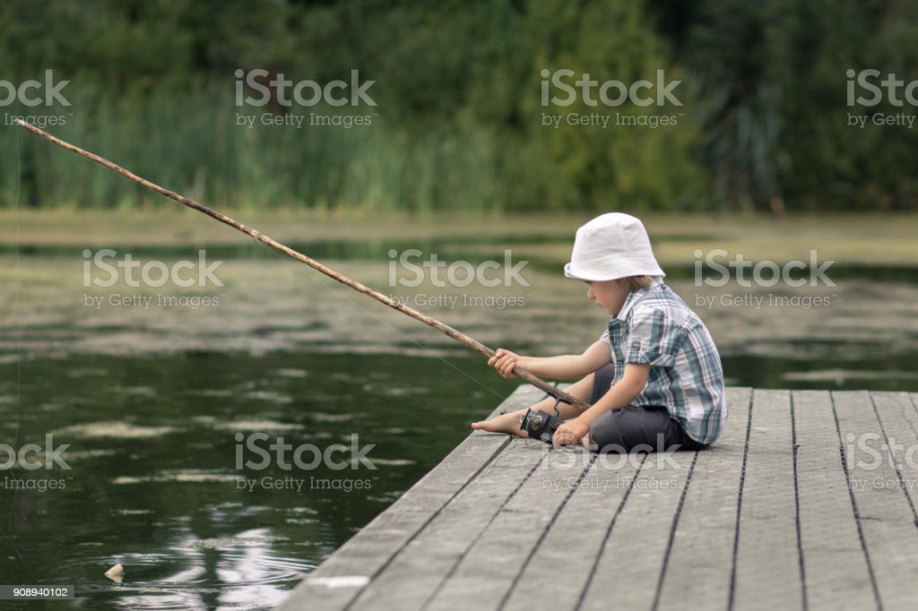 Little boy with old-fashioned fishing rod on a wooden pier stock photo