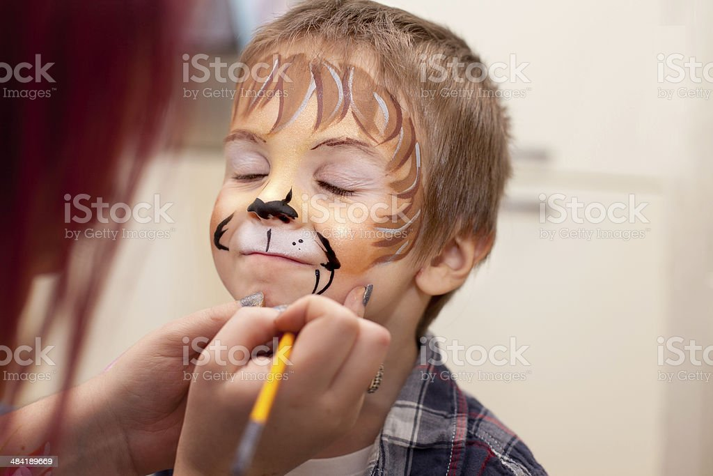 Little boy with painted face as a lion stock photo