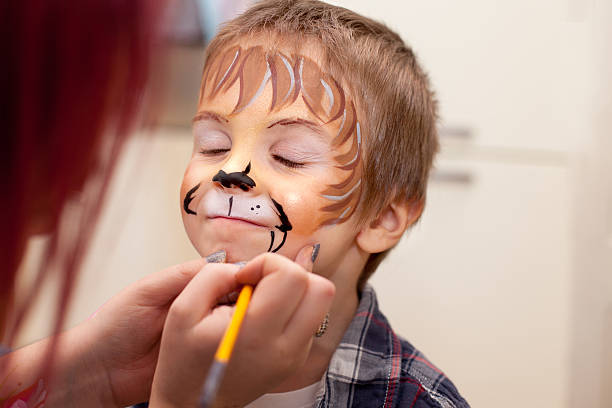 Little boy with painted face as a lion Little boy with painted face as a lion carnival children stock pictures, royalty-free photos & images