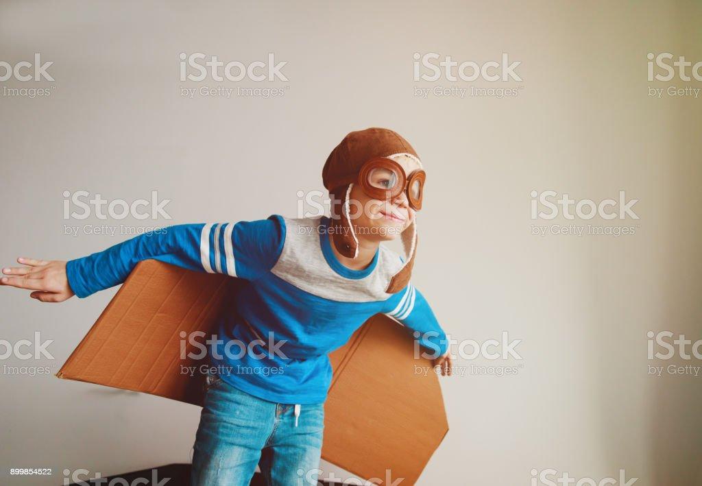 niño con gafas de piloto y alas juego en casa - foto de stock