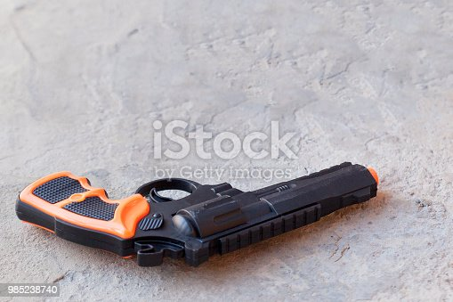 Little boy with plastic gun in the jeans pocket. Happy boy with toy pistol gun playing at outdoors.