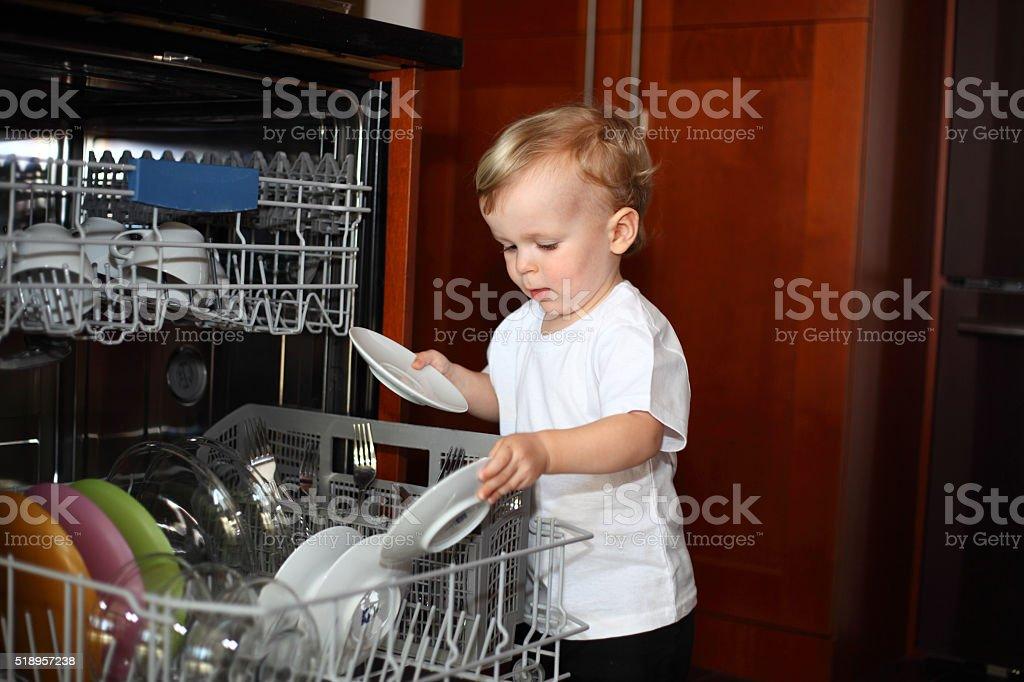 Little boy with plates near dishwasher stock photo