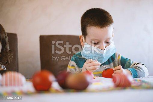 Little boy focused on painting Easter egg