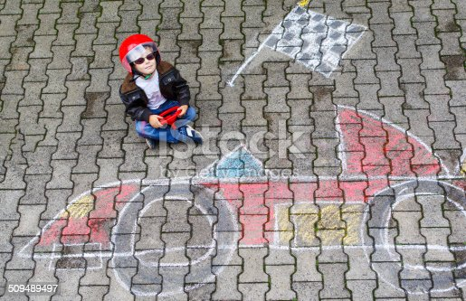 istock Little boy with race car picture drawing with chalk 509489497