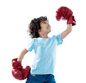 Little boy with red boxing gloves against white background.