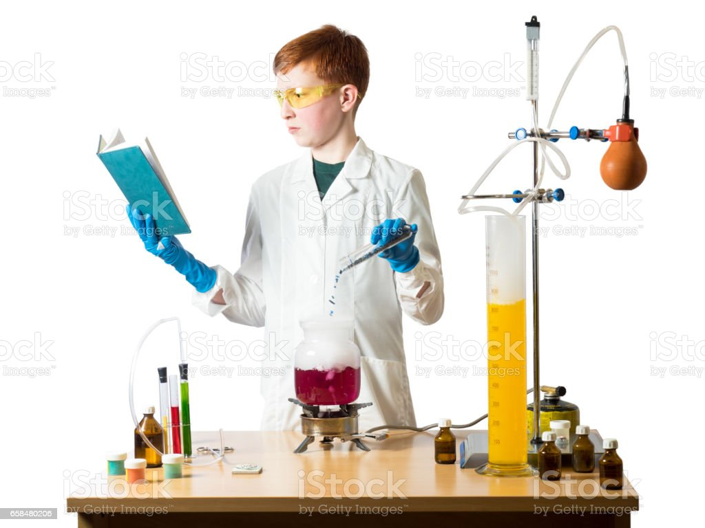 Little boy with red hair wearing glasses and lab coat holding a book and a glass flask on white background with table and chemical equipment stock photo