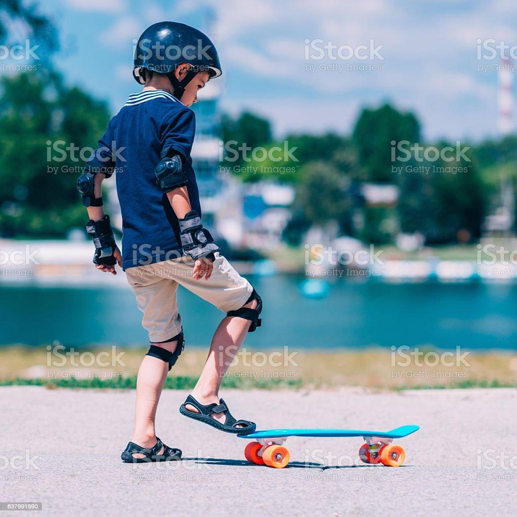 Little boy with skateboard stock photo