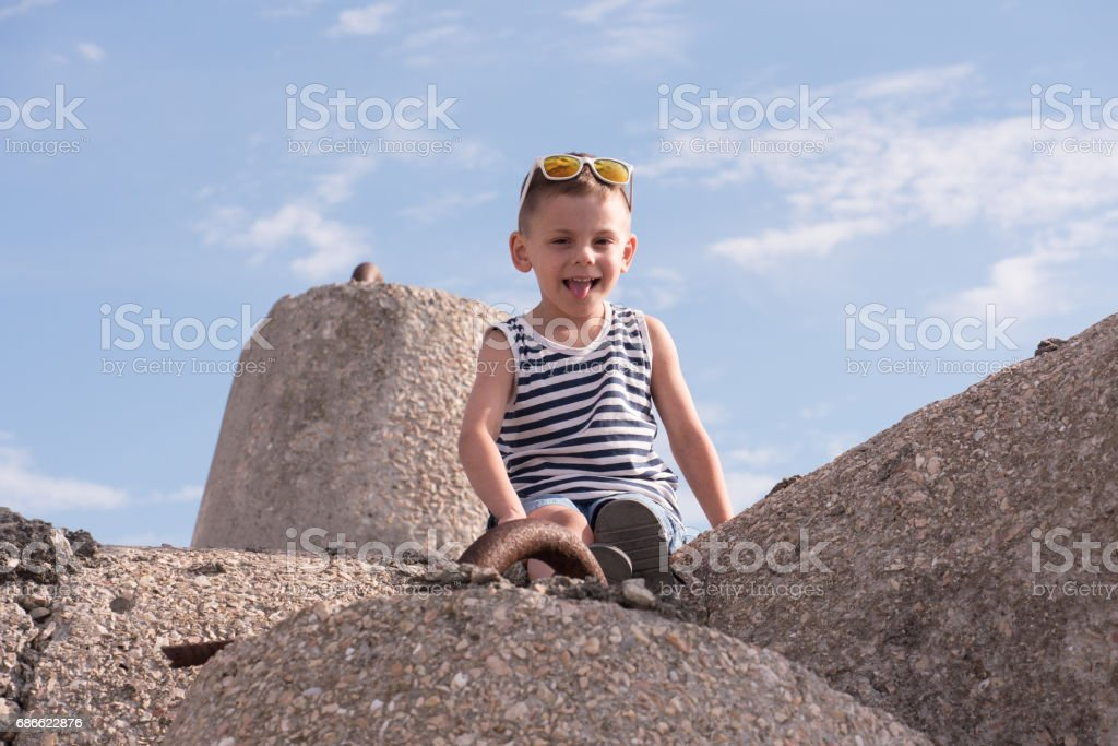 Little boy with sunglasses sitting on breakwater and showing tongue royalty-free stock photo