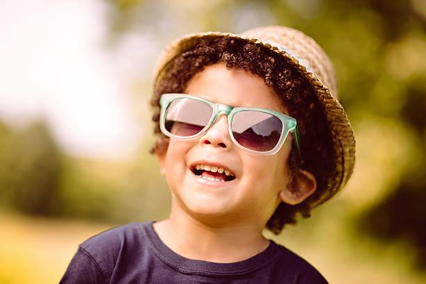 kleiner junge mit sonnenbrille lächelnd in der natur - sonnenbrille kleinkind stock-fotos und bilder